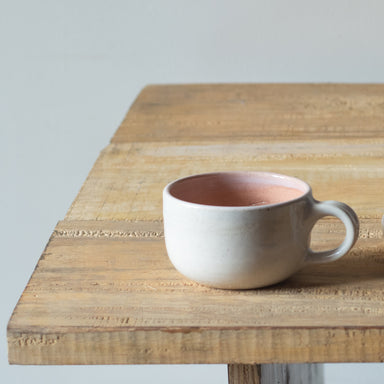 Peach, short mug, kept on a table