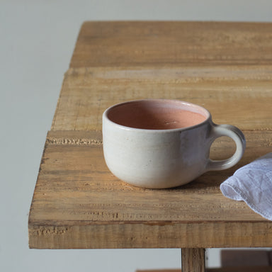 Peach, short mug by fleck, kept on a table