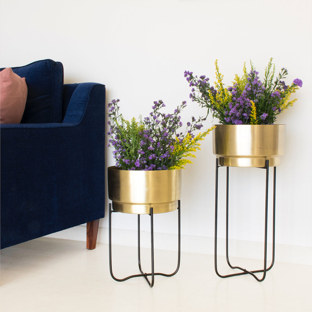 Two Matte gold planters with balck stands, and a blue couch in the background, Champagne Gold planters