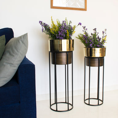 Two tall dual tone planters, gold and brown with black stands. Couch In foreground and painting in background.