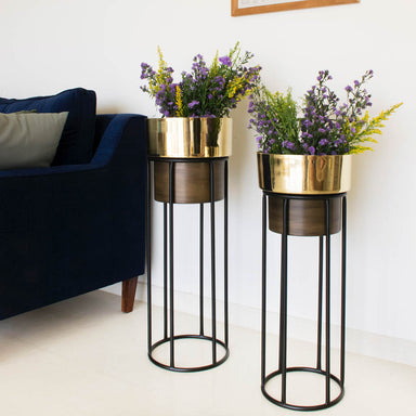 Two tall dual tone planters, gold and brown with black stands. Couch and painting in background.