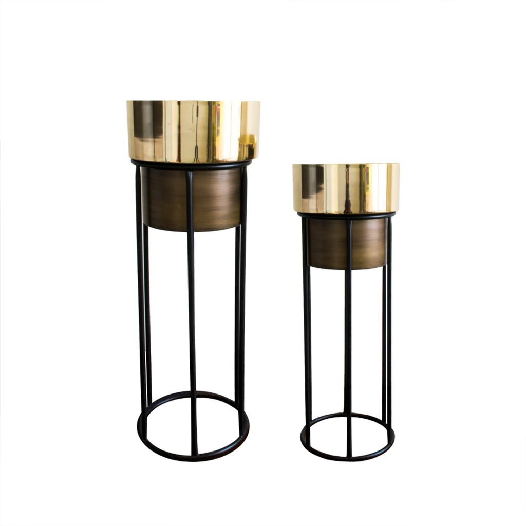 Two tall dual tone planters, gold and brown with black stands.