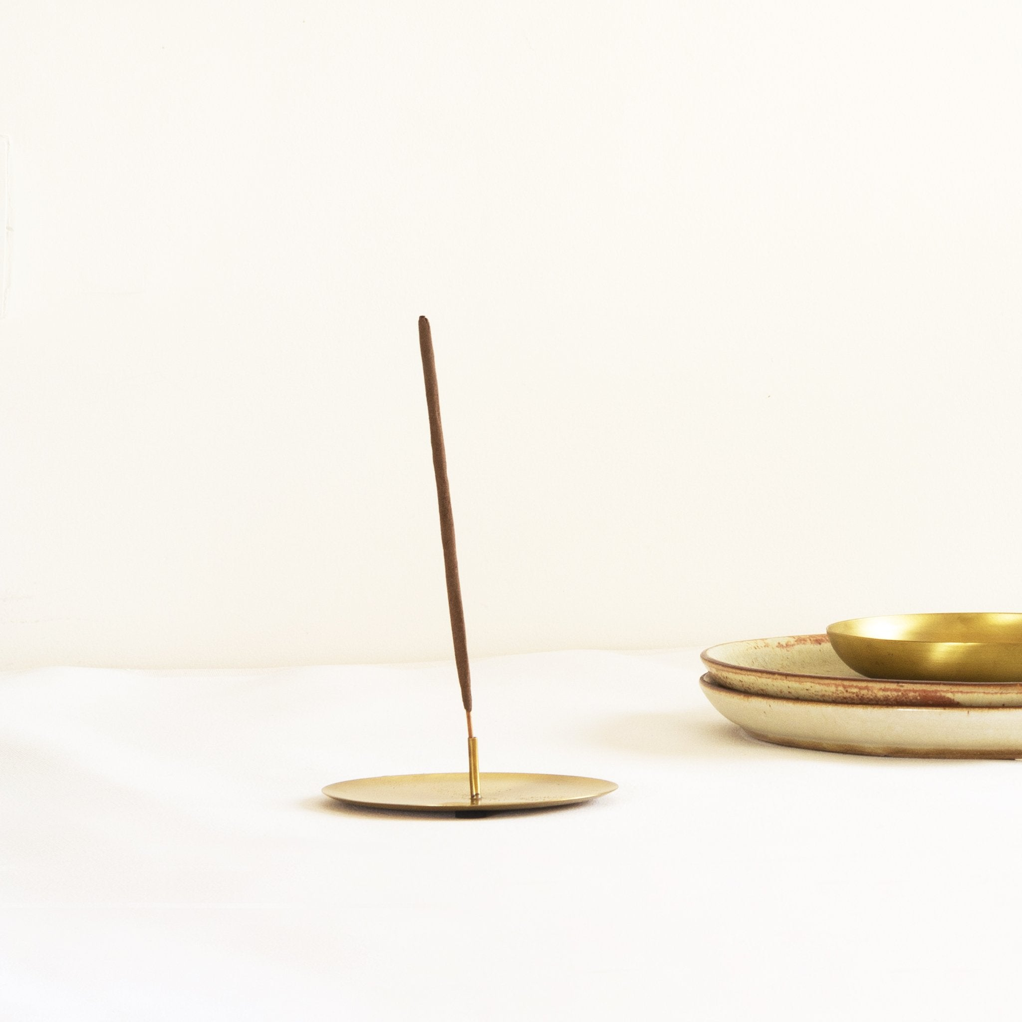 Brass Incense stick holder with two incense stick with ceramic plates in the background. Part of heirloom collection by Fleck India