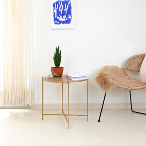 Copenhagen table with a plant and a book on top next to a chair with a painting in the background, made by Fleck India