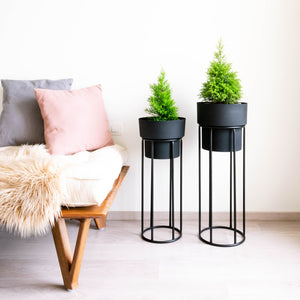 Two tall planters, Charcoal black pots with black stands. Bed & rug In foreground and painting in background.