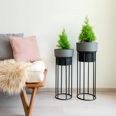 Two tall dual tone planters, slate and black with black stands, next to a daybed