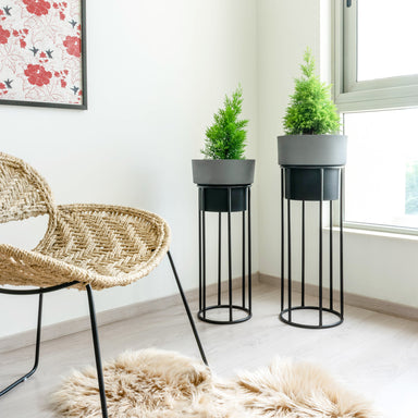 Two tall dual tone planters, slate and black with black stands. Chair & rug In foreground and painting in background.