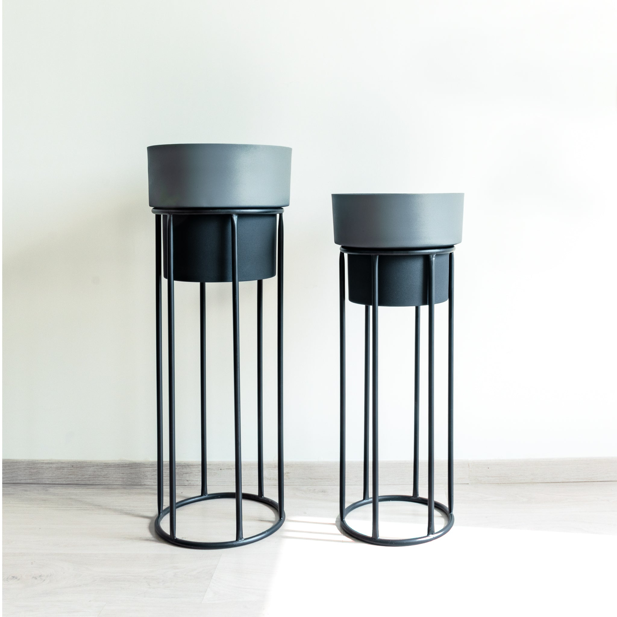 Two tall dual tone planters, slate and black with black stands.