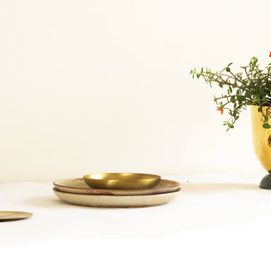 brass bowl on ceramic plates by fleck India. Part of heirloom collection.