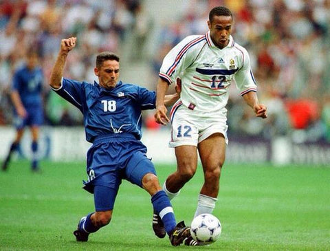 Thierry Henry sprints away from Angelo di Livio of Italy.