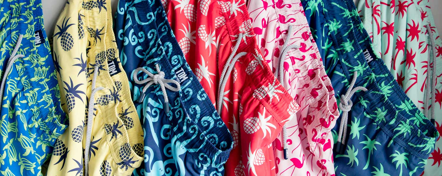 matching swimming trunks and clothing from Tom and Teddy showing a full range of swim shorts hangin up in different bright colours and designs from turtles, pineapples, octopus, flamingo, palm trees and more, perfect for father and son at the beach.