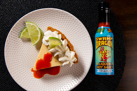 A bottle of Swamp Dragon Tequila Hot Sauce next to key lime pie topped with Tequila Dragon Hot Sauce