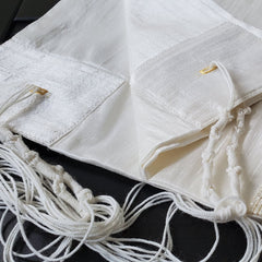 Silk tallit folded to show tzitzit