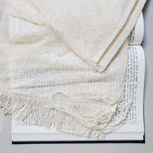 A handmade lace tallit in soft eggnog tones lays on a book of Torah text.