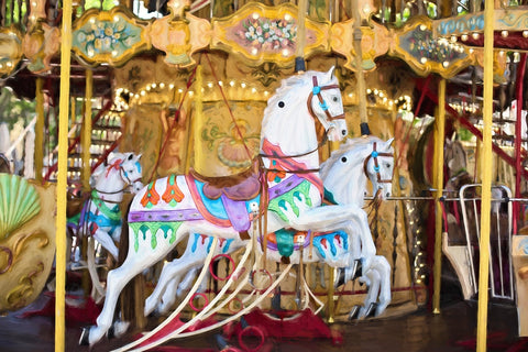 Vintage White Carousel Horse resplendent in magentas, aquas, greens and yellow decorations on a beautiful golden carousel. Surround Yourself with Beauty. The Roughshod Ribboniere.