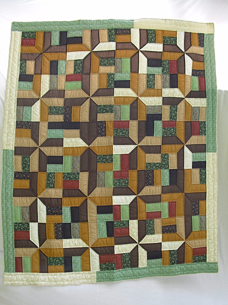 Autumn Approaching brand new, heirloom quality quilt handmade in Kentucky, USA in the Anvil Pattern using earth tones like dark brown, navy, rust inside a beautiful green and cream border. Hand-pieced. Hand-quilted. Artisan made. Exclusively online at RoughshodRibboniere.com
