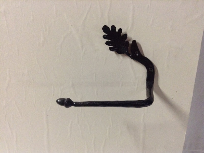 "Hand forged iron wall toilet paper holder with leaf and acorn accents. Black. 7"" x 6"" x 4""."