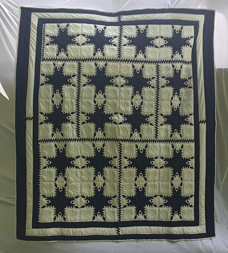 "Navy and white Feathered Star Pattern define this classic handmade, hand-pieced, hand-quilted blanket called Merry Mariner's Heirloom Quilt. 87"" x 99""."