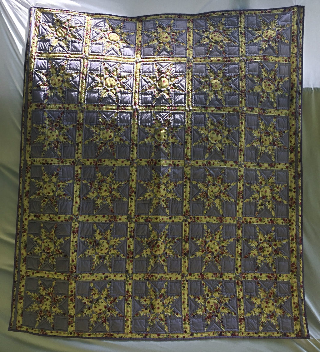 "Lemon yellow and lavender with red rosebuds in a Feathered Star pattern define this handmade, hand-pieced, hand-quilted quilt called Lovestruck in Lavender. 88"" x 102""."