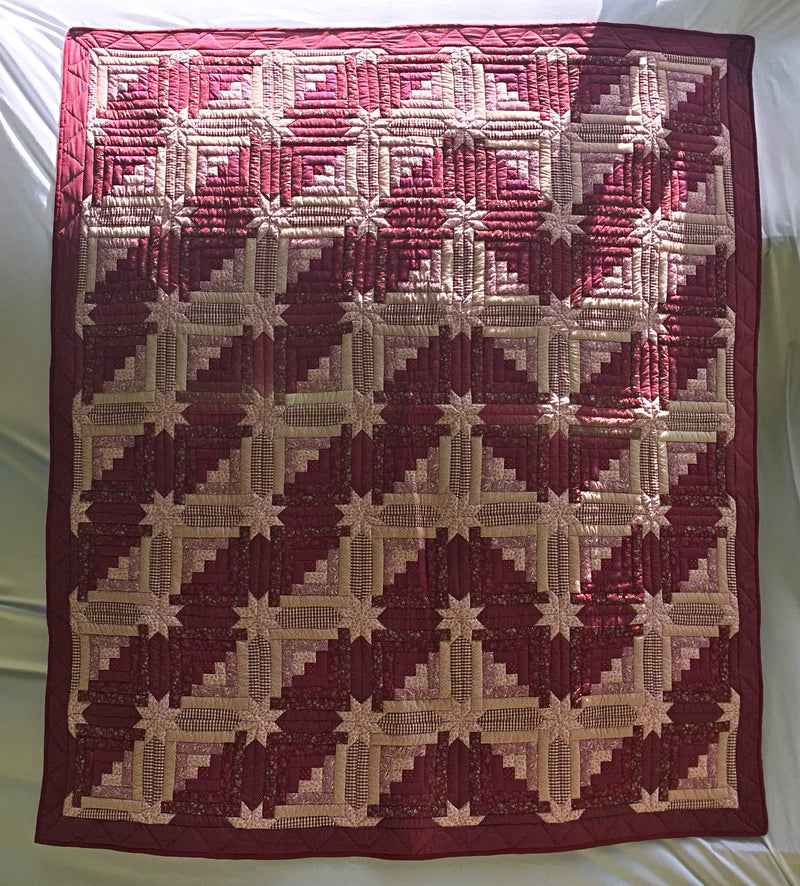 "Rocky Mountain Reverie handmade in Kentucky, USA quilt. Hand-pieced, hand-quilted in burgundy and pinks in a turned Log Cabin pattern. 91"" x 102""."