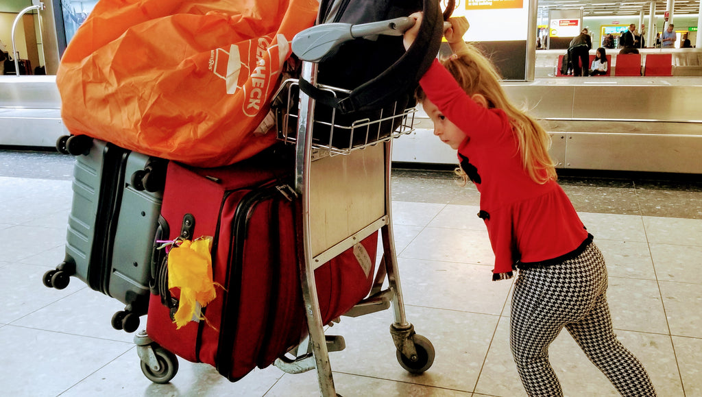 Xaria just loves trying to push the luggage - London Heathrow Airport