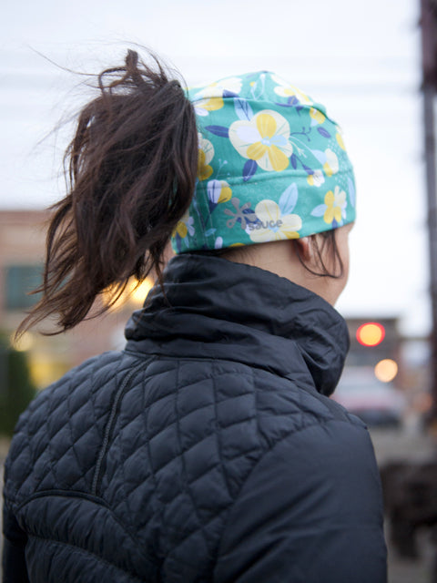 Floral patterned winter hat designed to be worn under helmets with pony tail hole