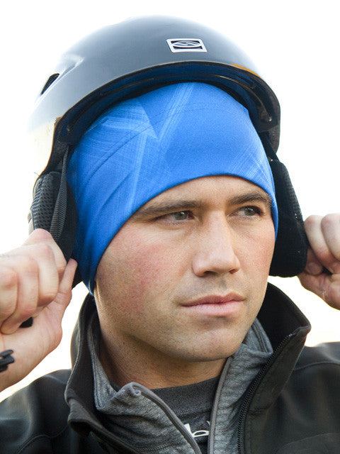 man putting a ski helmet over a blue helmet liner