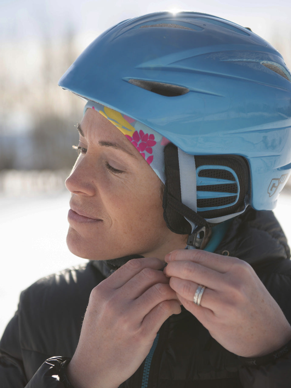 a woman wearing a ski helmet over a floral patterned winter hat