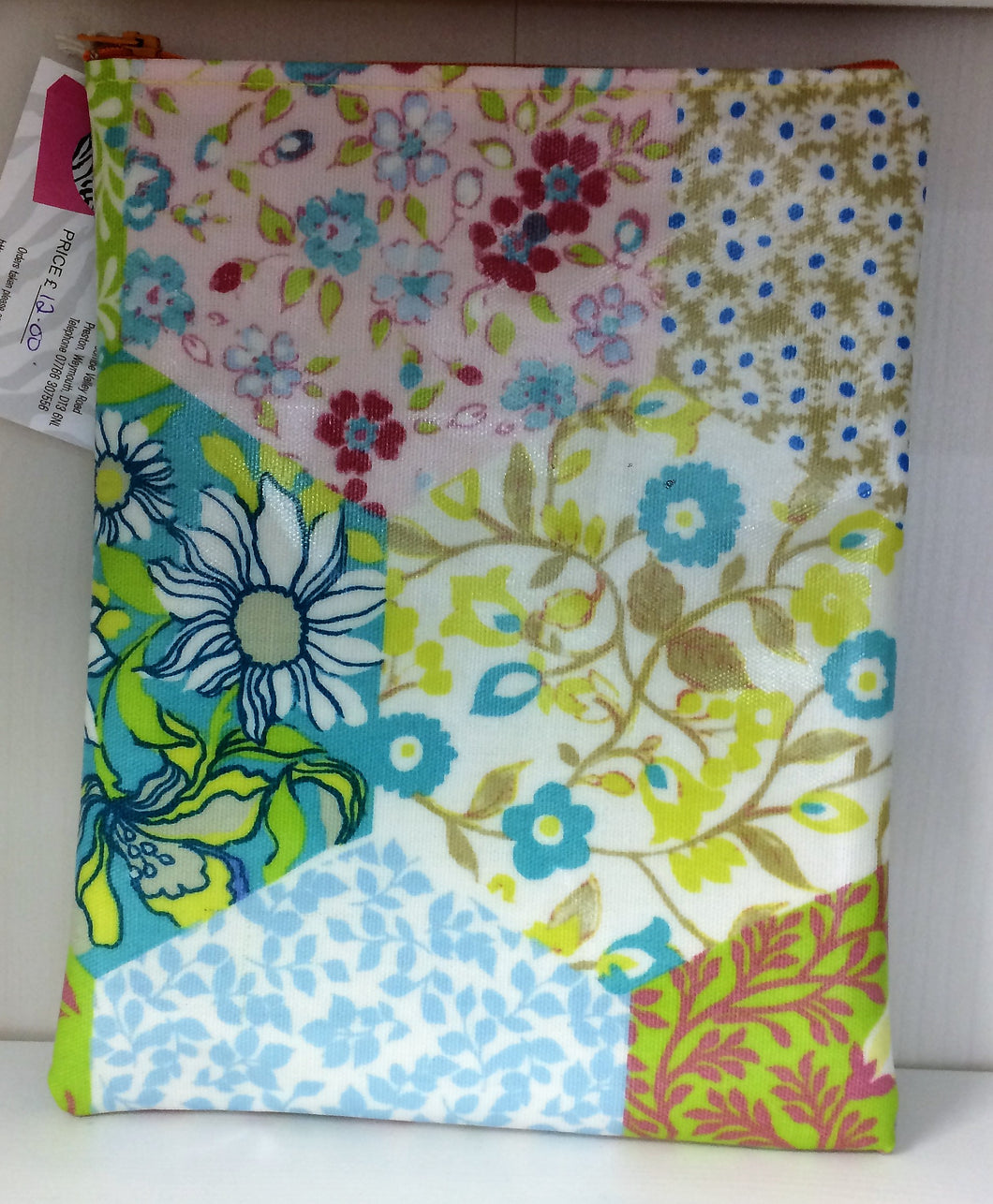 Waxed fabric floral  makeup bag with zipped top.