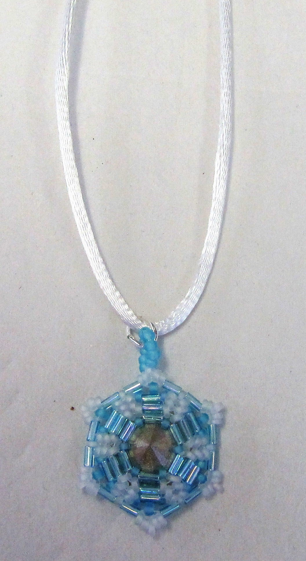 Handcrafted blue beaded pendant on white cord necklace