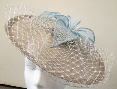 Handcrafted pewter disk fascinator with silver netting and blue leaves on a hair band