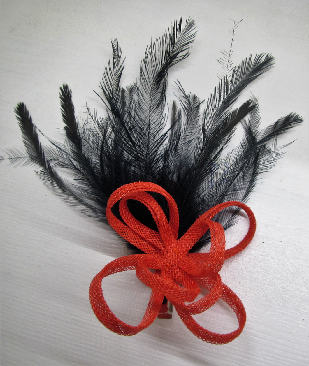 Handcrafted burnt orange bow fascinator with navy blue feathers on a clip