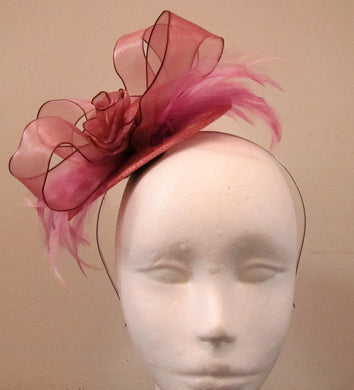 Handcrafted small pink flower and feather fascinator on a headband