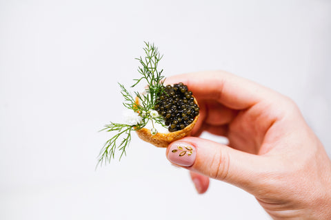 Russian Ossetra Caviar with beautiful grains in held in a hand.
