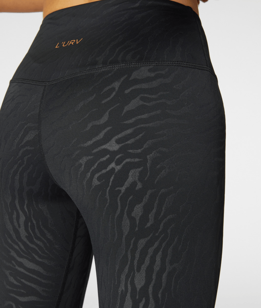 L'URV's Step UpLeggings are high waisted, full-length compression leggings in a black tiger print. They have 2 thigh pockets.