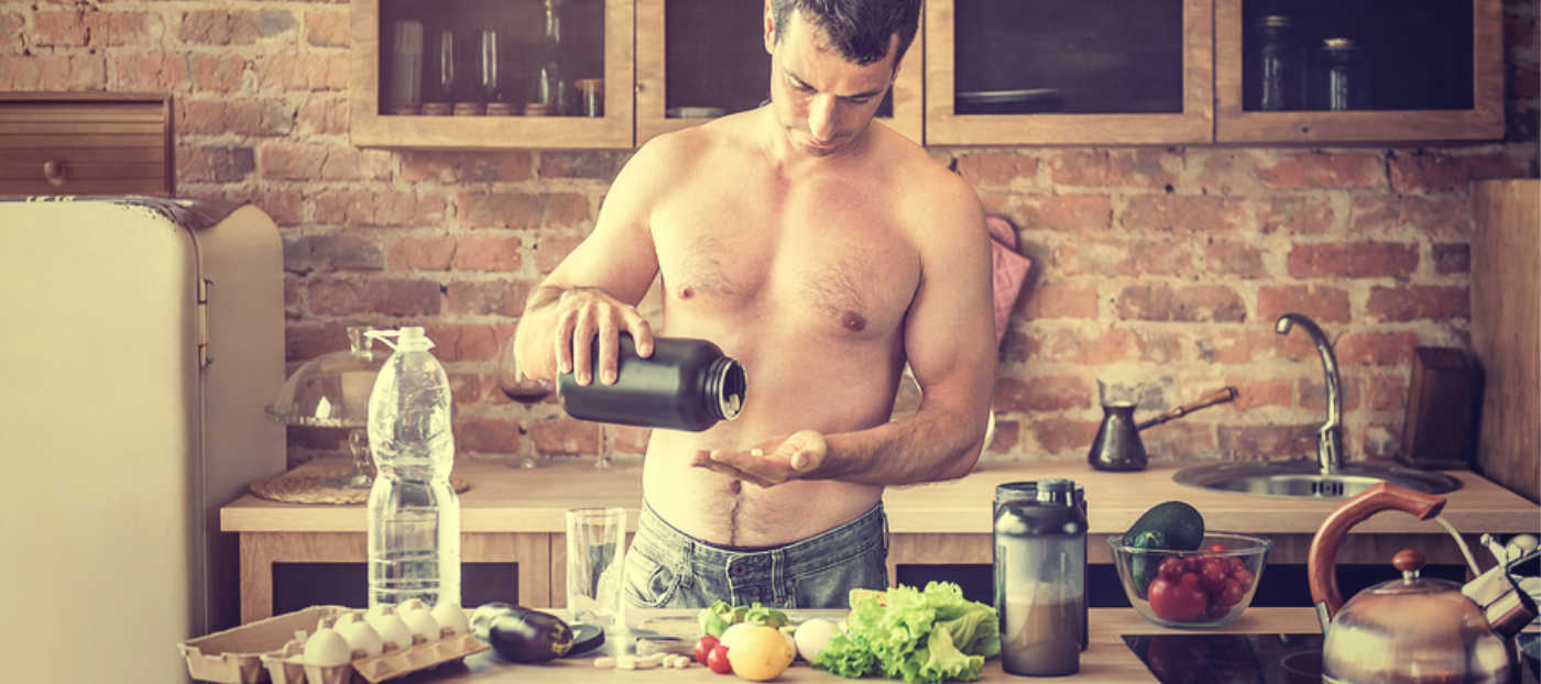Athlete taking supplement in kitchen