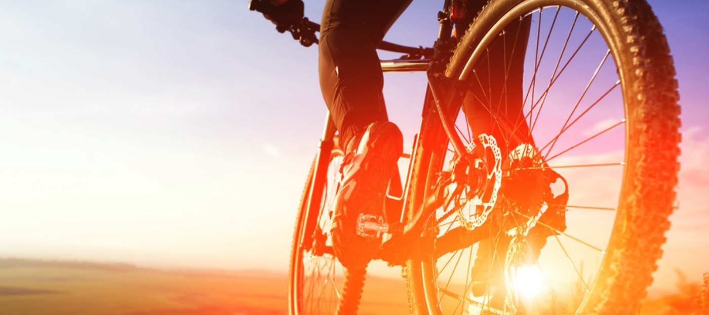 cyclist riding into sunset