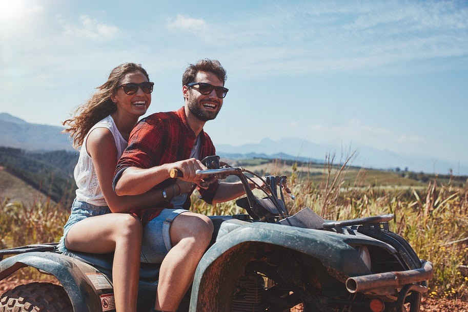 Happy young couple driving a quad bike