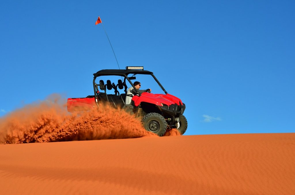 A man driving a four wheeler on the sand causing sand to fly with a beautiful blue sky background.