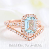 Emerald cut aquamarine halo ring and contoured diamond wedding band in rose gold bridal set by la more design jewelry