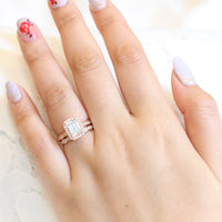 Emerald cut moissanite halo ring and matching diamond wedding band in rose gold bridal set by la more design jewelry