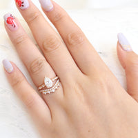 Solitaire pear moissanite ring and curved crown diamond wedding band in rose gold bridal set by la more design jewelry