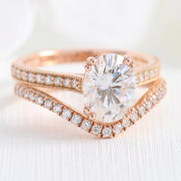 Solitaire pear moissanite ring and curved diamond wedding band in rose gold bridal set by la more design jewelry
