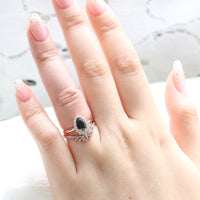 pear engagement ring rose gold halo black diamond ring and salt and pepper grey diamond wedding band by la more design jewelry