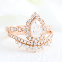 vintage inspired pear moissanite ring and crown diamond wedding band in rose gold bridal set by la more design jewelry