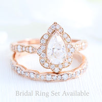vintage inspired pear moissanite ring and matching diamond wedding band in rose gold bridal set by la more design jewelry