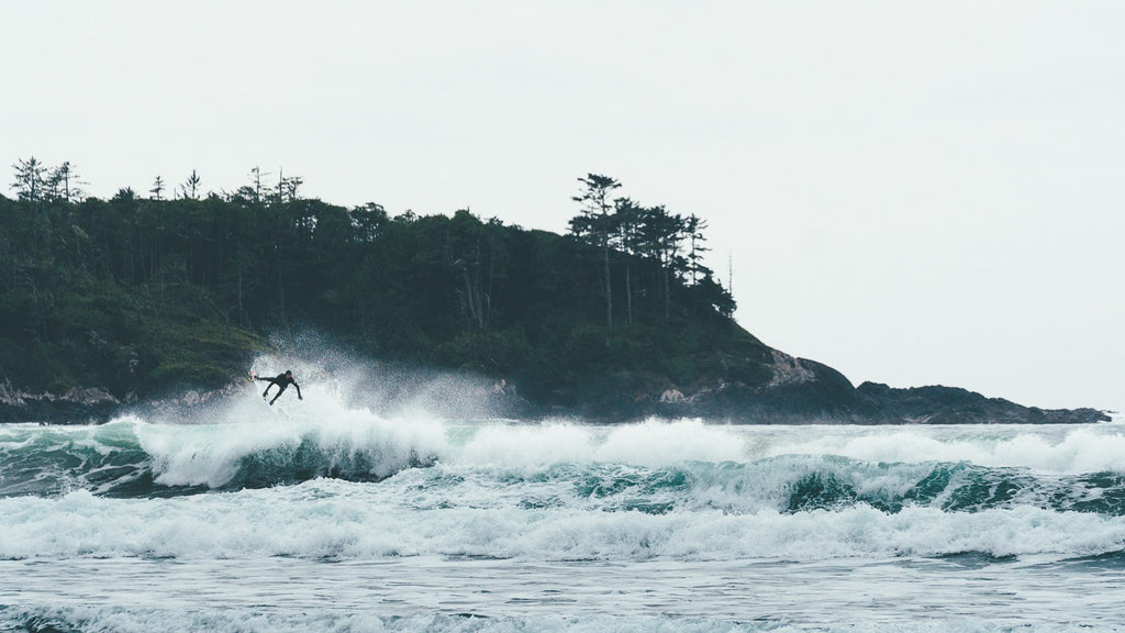 Surfer catching air at Cox Bay in Tofino, British Columbia