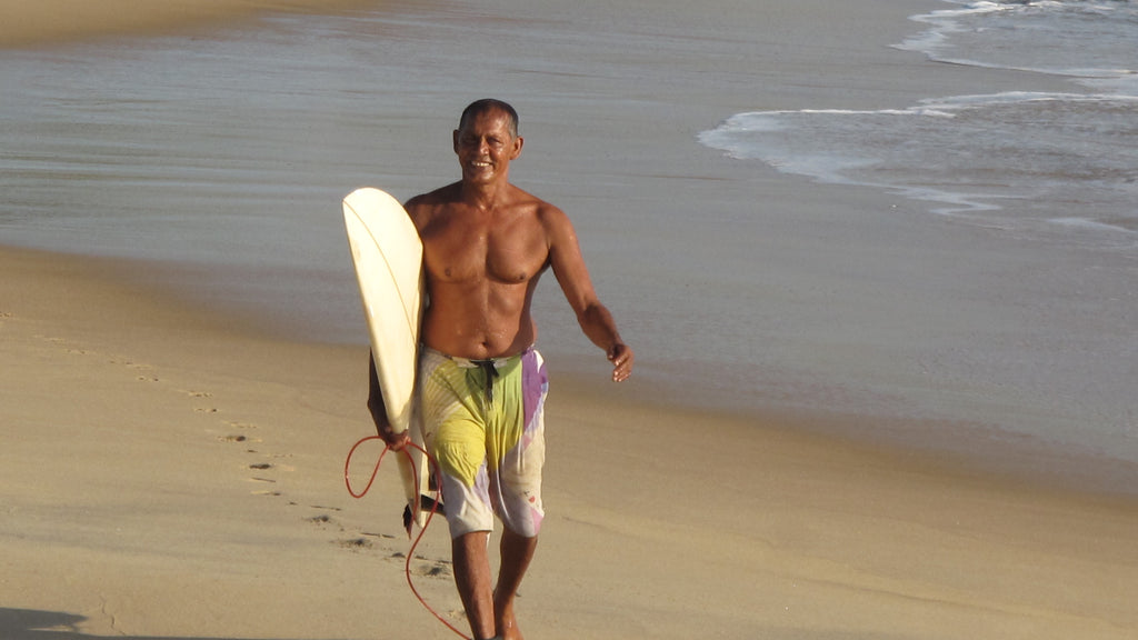 Jaya walking out of surf with board in hand with a big smile
