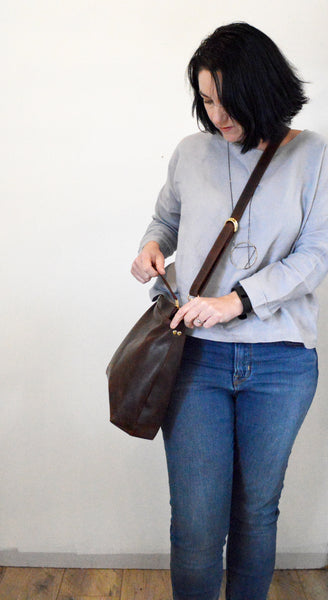 Dark brown leather hobo bag worn as a crossbody bag