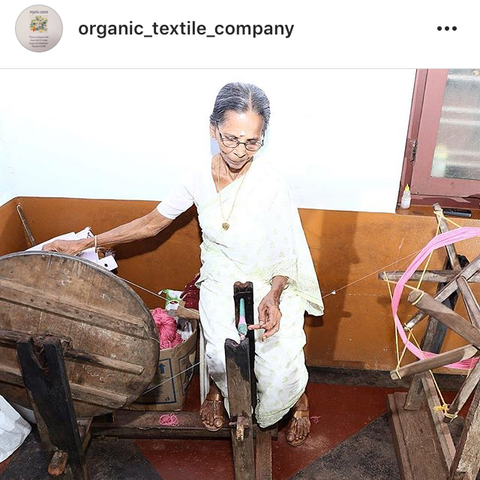 Textile worker in Kerala, India, winding organic cotton yarn to prepare for weaving fabric